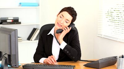 stock-footage-brunette-woman-answering-the-phone-at-work
